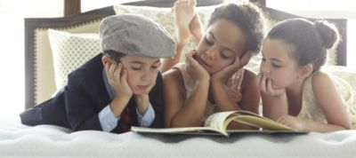 Children reading on a comfortable Stearns and Foster mattress